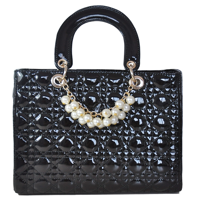 Elegant lady with a pearl pendant patent leather bag